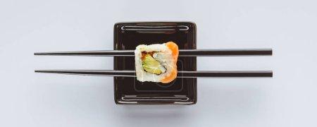 美味寿司与白色筷子的特写视图