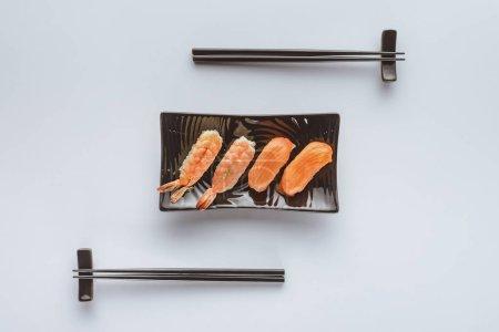 美味寿司与鲑鱼和虾在板上和筷子上的白色分离