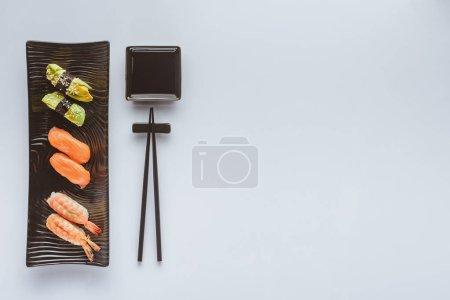 在白色的各种美食寿司和筷子的顶级视图