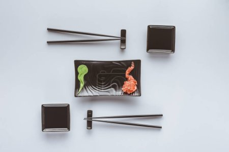 筷子和芥末的顶部看法在白色被隔绝的寿司吃姜