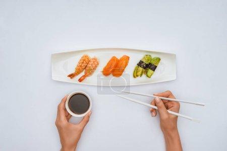 手持筷子和碗酱油的人在吃白色的寿司时被裁剪的镜头
