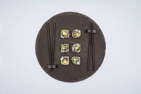在白色的圆形石板板上的美味寿司和筷子的顶级视图