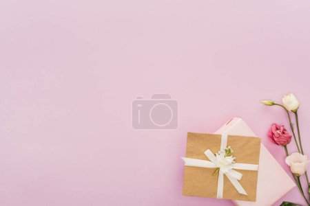 在粉红色与复制空间隔离的礼品盒和鲜花的顶部视图