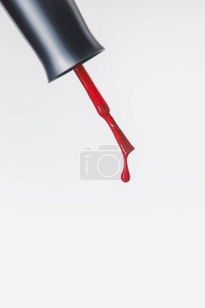 指甲油刷与红色下降隔离在灰色