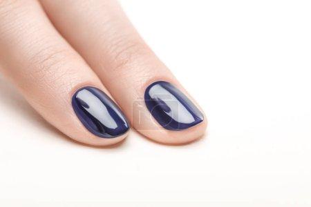 指甲与闪亮的海军蓝色指甲油在白色背景