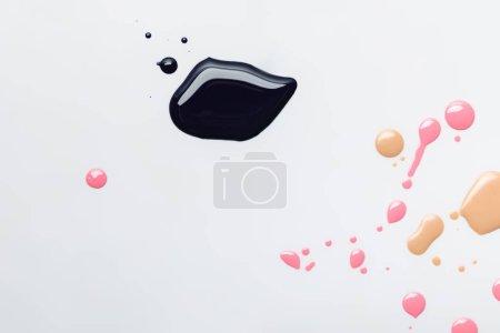 最高视图湿黑色泄漏粉红色和米色滴隔离在灰色