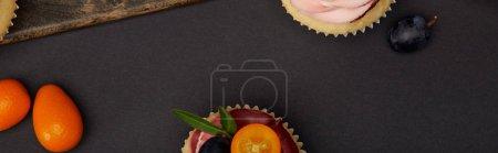 panoramic shot of cupcakes with kumquats on black surface