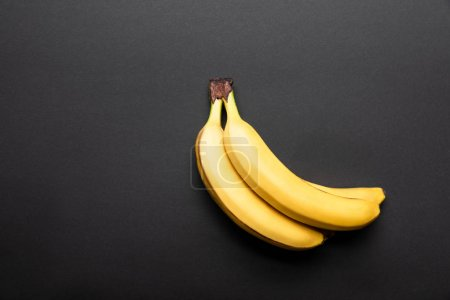 top view of ripe yellow bananas on black background with copy space