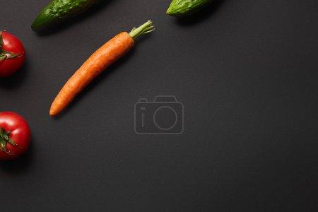 原始胡萝卜、黄瓜和西红柿的顶视图在黑色背景与拷贝空间