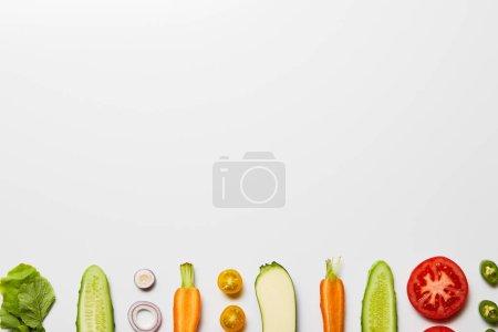 平躺在白色背景上的切片有机蔬菜与复制空间