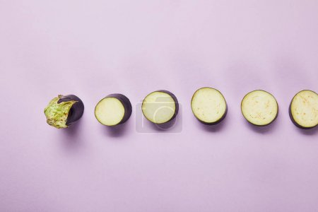 top view of ripe sliced eggplant on violet background with copy space