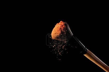 化妆刷与橙色粉末在黑色背景