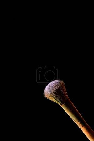 化妆刷与彩色紫罗兰粉隔离在黑色