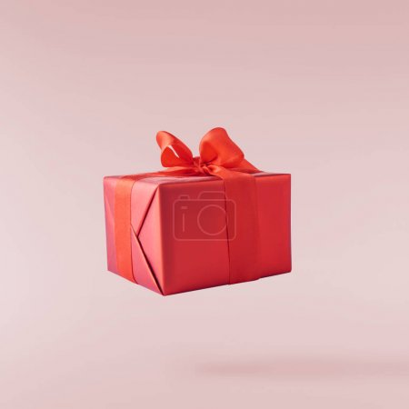 Valentines day concept.  Creative valentines day conception made by falling in air gift boxes and red hearts isolated on pink background