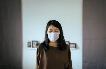 亚洲妇女使用口罩保护Pm 2.5因为污染在家里,年轻女性得到鼻子过敏