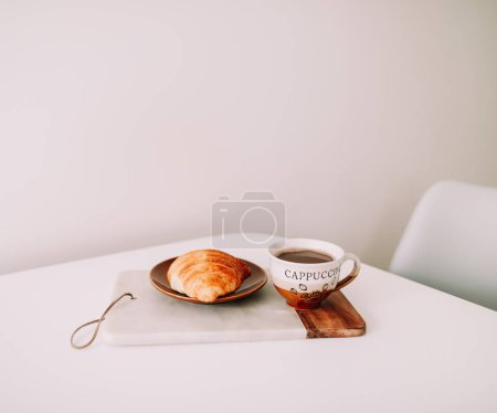 Cup of hot coffee and croissant for breakfast on white background