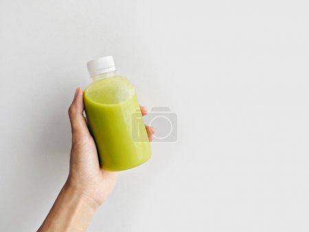 Hand holding fresh and healthy avocado juice in a bottle isolated on a white background, copy space