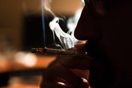 在黑色背景下吸烟的男子, 吸烟成瘾