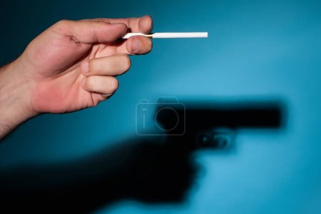 Cigarettes are killing. Damage to health from smoking. Cigarette gun. The shadow of a cigarette. Bad habit of smoking. Damage to health from smoking cigarettes.