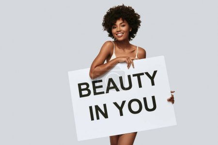 happy attractive young African woman covering body with poster with message beauty in you