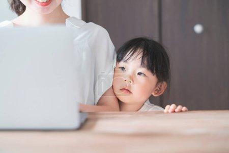 亚洲小女孩依偎在妈妈身边在家远程工作