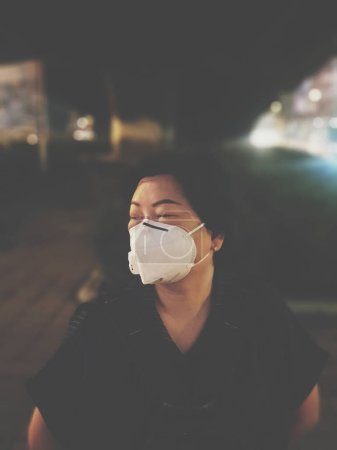 妇女使用N95面罩保护烟雾Pm2.5灰尘在城市