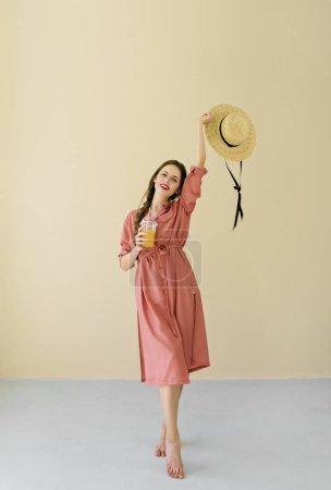 微笑的年轻妇女与夏天帽子举行果汁在米色背景