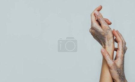 女性的手覆盖在银色闪亮的闪光