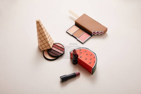 powder with eyeshadows and decorative ice-cream with lipsticks on beige background, close view, beauty concept