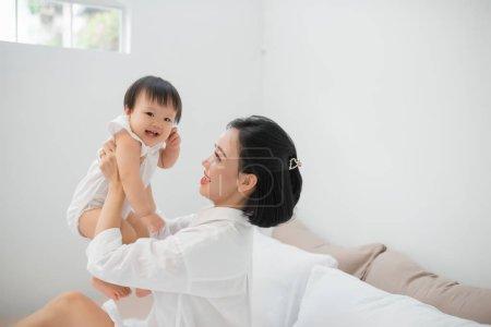 快乐的爱的家庭。母亲和她的女儿女孩在床上玩和拥抱.