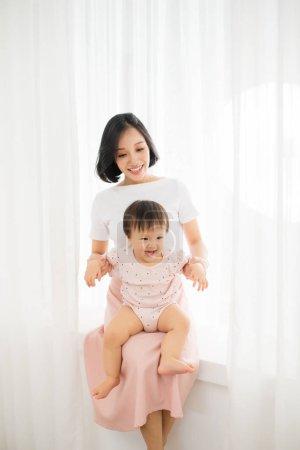 年轻的母亲抱着一个婴儿站在薄纱