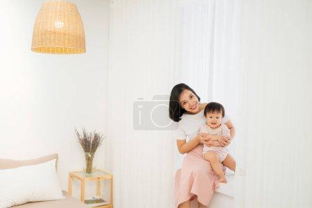 母亲节快乐!妈妈和她的女儿女孩在玩,微笑和拥抱