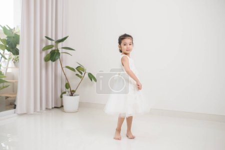 Happy cute preschooler girl dancing in living room
