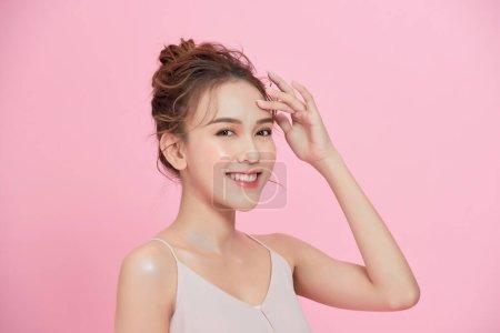 美丽而快乐的女人面对化妆品的概念健康而洁净的皮肤天然地隔绝在粉红的背景下.