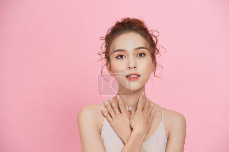 美丽快乐的女人面对化妆品的概念健康洁净的皮肤粉红的背景