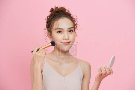 年轻美丽的亚洲女人在化妆,照镜子