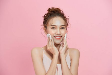 健康新鲜的女孩,从她的脸,用化妆棉卸妆.