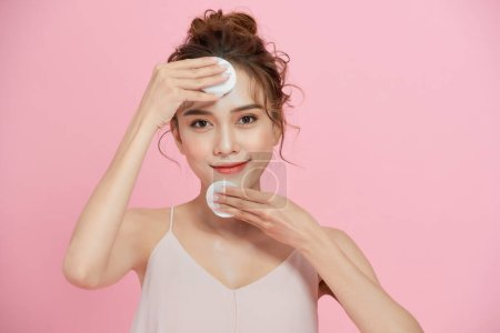 一个面带微笑的迷人女人用粉色背景上的棉垫擦拭她的脸的特写