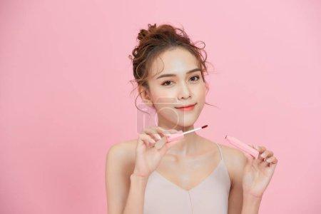 年轻微笑的亚洲女孩涂唇膏,用粉红的背景隔开.
