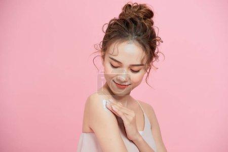 年轻的亚洲女人在她的皮肤手臂上涂奶油/乳液。与粉红背景隔离.