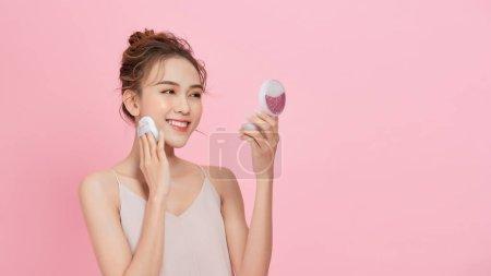 年轻迷人的亚洲女士在脸庞上涂上粉状粉扑粉,粉红底色.