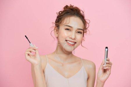 一个漂亮的年轻姑娘的肖像,手上拿着睫毛刷,背景是粉色的.