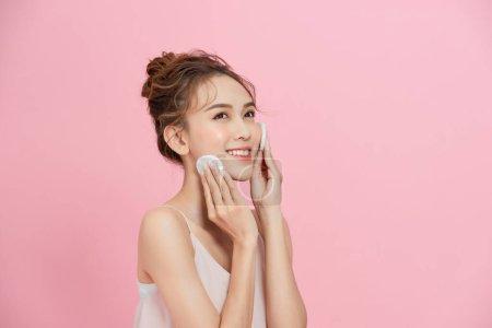 美丽的亚洲女孩,皮肤完美,用棉垫化妆,洗脸的概念.