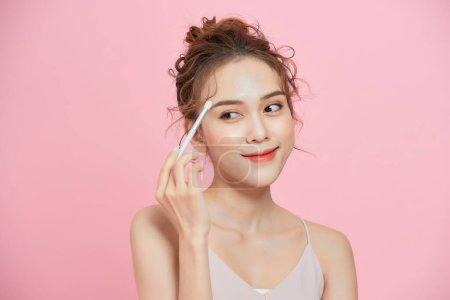 兴奋的年轻亚洲女人手握画笔,在粉色背景上化妆的肖像.