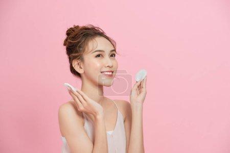 美丽的亚洲女人,棉垫与粉红背景隔离.