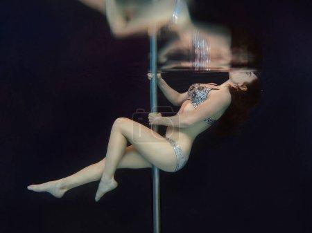 年轻,适合,苗条的女人在游泳水晶胸罩和内裤与杆水下在游泳池的黑色背景