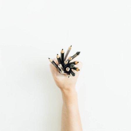 妇女手拿着一束铅笔在白色背景。平的放置, 顶部看法极小的艺术家构成.