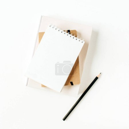 Minimalist office desk workspace with notebook on white background. Flat lay, top view blank paper copy space mock up.