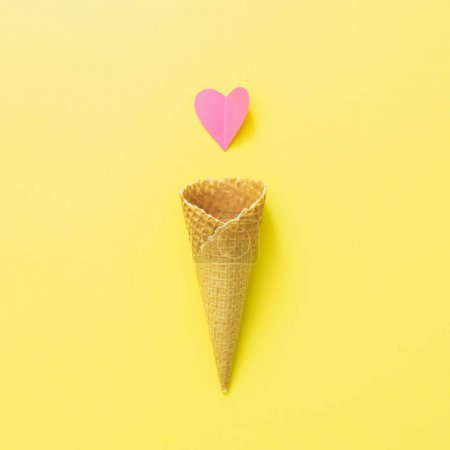 Waffle cone of ice cream and paper pink heart. Love sweet food. Summer concept